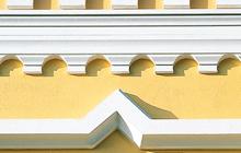 Außenbereich von Oskar Seus gelbe Außenwand mit weißer Fassadenverzierung