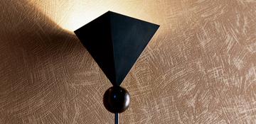 Startseite von Oskar Seus braun strukturierte Wand mit Lampe